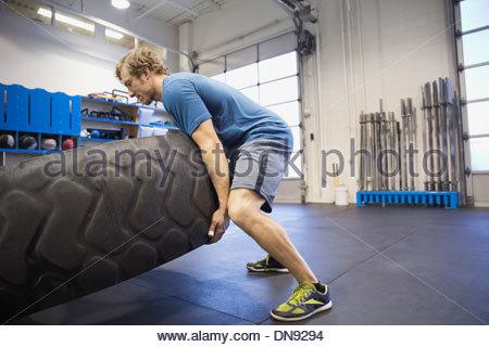 Uomo che fa del pneumatico-flip esercizio in palestra Crossfit Foto Stock