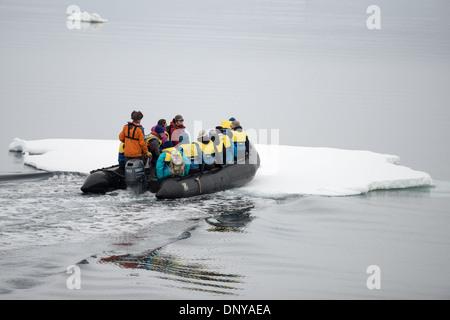 Antartide - un Zodiac con i turisti si rompe attraverso un sottile foglio di mare di ghiaccio nei pressi di Galindez Foto Stock