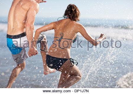 Giovane giocando in onde sulla spiaggia Foto Stock