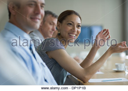 Imprenditrice sorridente in riunione nella sala conferenze Foto Stock