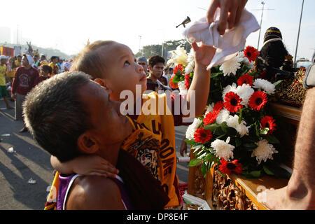 Manila, Filippine . 9 Gen, 2014. Un giovane bambino ottiene una salviettina da una replica del Nazareno nero a Manila Foto Stock