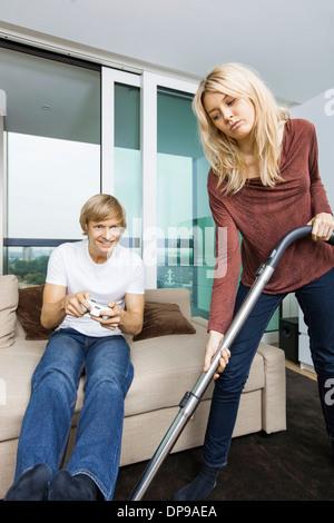Donna di aspirare mentre l uomo video gioco nel salotto di casa Foto Stock