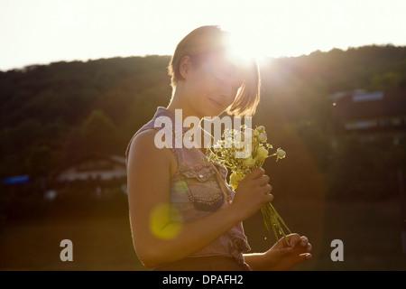 Giovane donna in prato azienda mazzetto di fiori selvatici Foto Stock