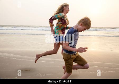 Madre e figlio in esecuzione sulla spiaggia Foto Stock
