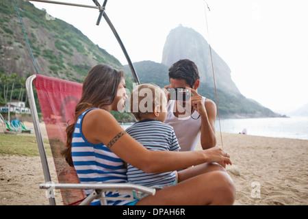 L'uomo prendendo fotografia di madre e figlio sulla sedia, Rio de Janeiro, Brasile Foto Stock