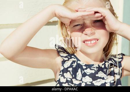 Bambino che copre la sua gli occhi dai riflessi del sole Foto Stock