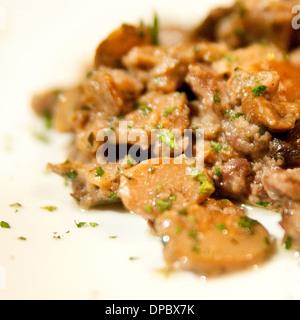 Spezzatino di manzo con funghi e prezzemolo. sulla piastra bianca Foto Stock