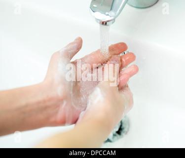 Il lavaggio delle mani con sapone in bagno vicino fino Foto Stock