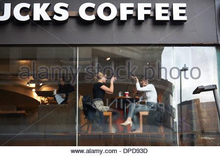Coppia avente una tazza di caffè e di parlare come visto attraverso la finestra dalla strada di Starbucks in New Oxford Street, Londra Foto Stock