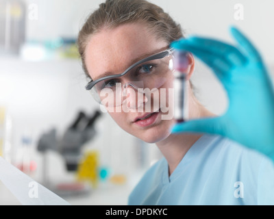 Tecnico azienda con codice a barre campione di sangue nel laboratorio clinico Foto Stock