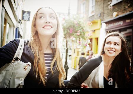 Giovani donne camminando per strada il trasporto del bagaglio e ridere Foto Stock