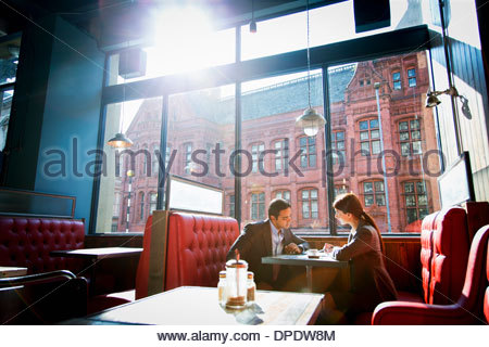 Giovane seduto in cabina di ristorante Foto Stock