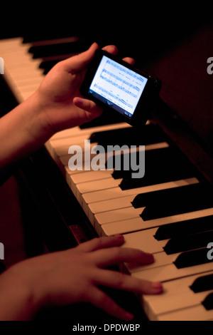 Close up di mani utilizza lo smartphone durante la riproduzione del pianoforte Foto Stock