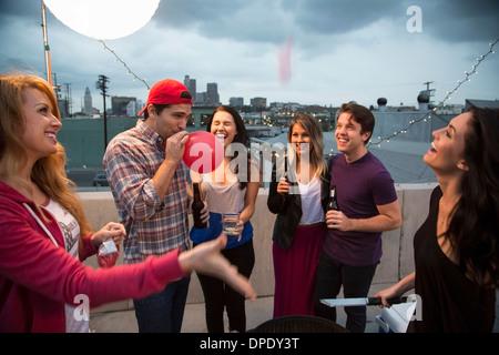 Giovani amici adulti ingannare intorno al barbecue Foto Stock