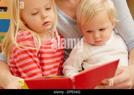 Lettura madre libro immagini con due figlie Foto Stock