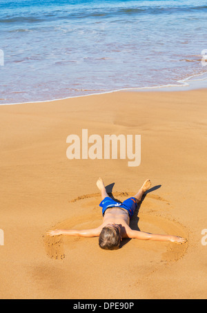 Felice carino ragazzino che posa sulla sabbia calda sulla spiaggia tropicale in Hawaii Foto Stock