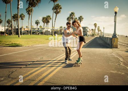 Giovane donna su skateboard a San Diego beach, ragazzo aiutando Foto Stock