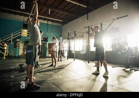 Uomo e personal trainer il sollevamento barbell in palestra Foto Stock