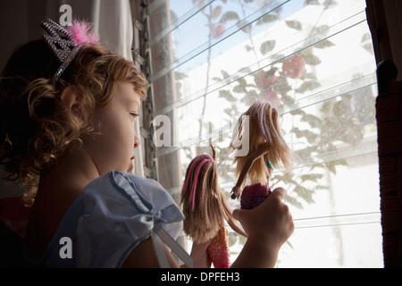 Toddler femmina guardando fuori della finestra tenendo premuto fino bambole Foto Stock