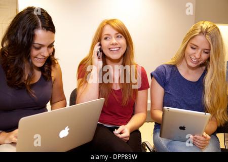 Tre ragazzi che usano i prodotti Apple - Macbook air laptop, un iphone % e un ipad, Essex REGNO UNITO Foto Stock