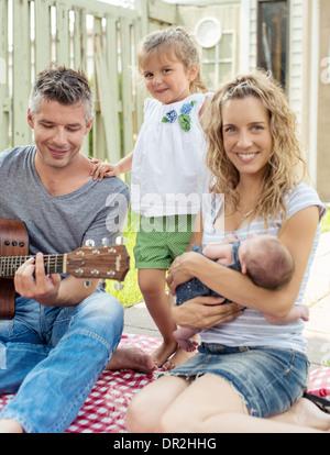 Padre suonare la chitarra su un picnic in famiglia Foto Stock