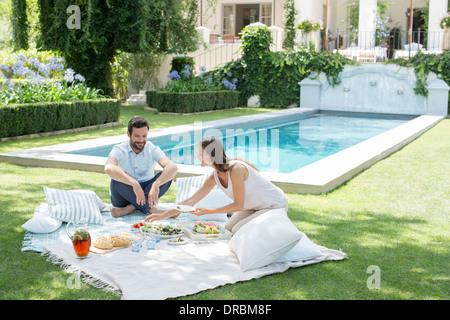 Giovane godendo picnic in piscina Foto Stock