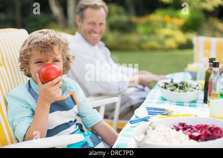 Ragazzo giocando con il cibo in tavola in cortile Foto Stock