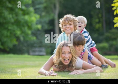 I bambini la posa su madre in erba Foto Stock