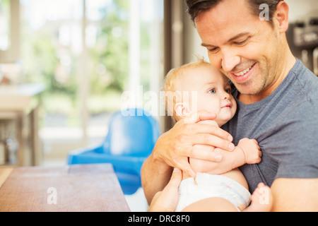 Padre tenendo il bambino in cucina Foto Stock