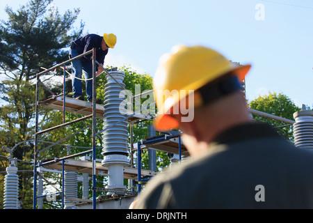 Ingegnere di potenza di eseguire interventi di manutenzione sul riempito di fluido di isolatore per alta tensione, Foto Stock