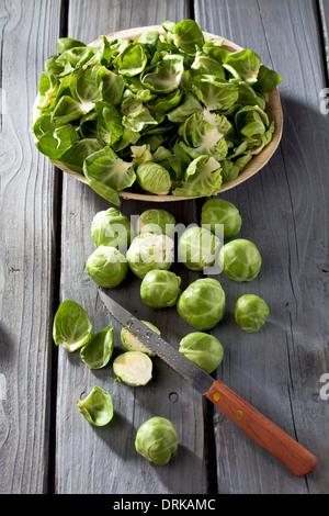 I CAVOLI DI BRUXELLES, piastra con bucce e coltello da cucina su grigio tavolo in legno Foto Stock