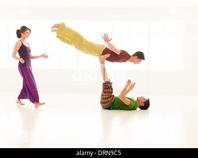 Tre giovani una donna e due uomini pratica yoga partner in classe sulla finestra di sfondo Foto Stock