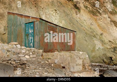 Una vecchia capanna arrugginito alla base di una rupe Foto Stock