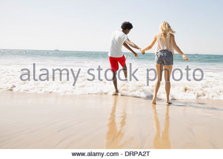 Giovane wading nel surf Foto Stock