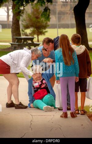 Gli amici che circondano un donna anziana dopo una caduta durante una raccolta di fondi a piedi in Cista Mesa, CA