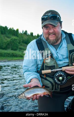 Fisherman tenendo un piccolo ruscello estate trota pescata la pesca con la mosca in un nord del lago Ontario Foto Stock