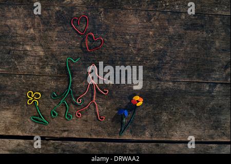 Creative love story, matura in amore, cuori e fiori realizzata da graffette e thumbtacks su un bellissimo sfondo di legno. Foto Stock