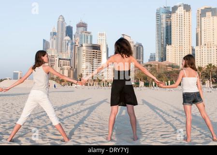 La madre e le figlie tenendo le mani alla spiaggia, vista posteriore Foto Stock