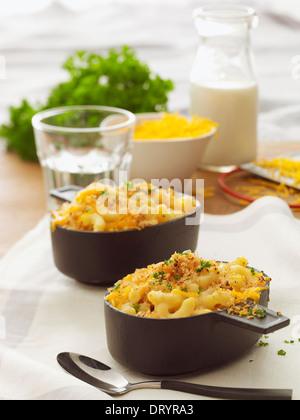 Due porzioni di maccheroni al forno e formaggio con prezzemolo guarnire, una ciotola di formaggio e un bicchiere Foto Stock