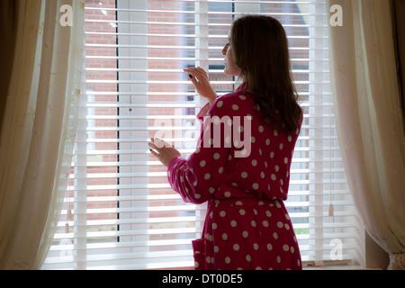 Silhouette di donna che indossa una vestaglia guardando fuori della finestra. Sulla spalla vista posteriore/laterale. Foto Stock