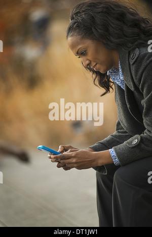 Una donna in un rivestimento di controllo e texting mantenendo in contatto utilizzando un telefono cellulare Foto Stock