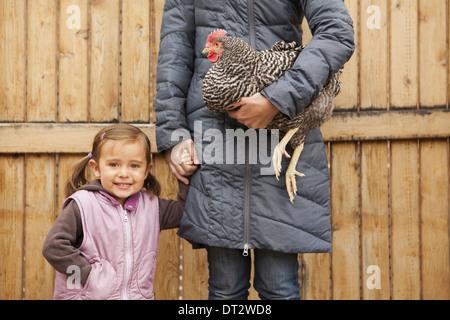 Donna che mantiene un bianco e nero il pollo con un rosso coxcomb sotto un braccio di una giovane ragazza accanto a lei mentre tiene il suo altro lato