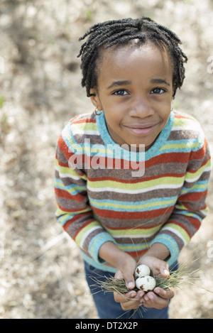 Un piccolo ragazzo in una camicia a righe tenendo un nido con tre uova di volatili Foto Stock