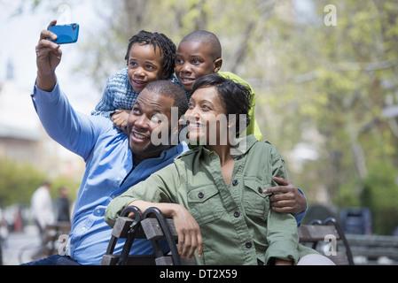 Una famiglia di genitori e due ragazzi di scattare una fotografia con un telefono intelligente Foto Stock