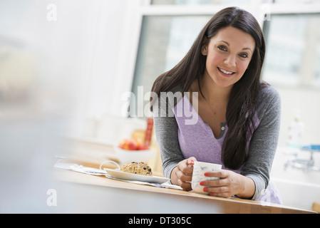 In un ufficio o un interno dell appartamento a New York City una giovane donna con lunghi capelli neri avente una Foto Stock