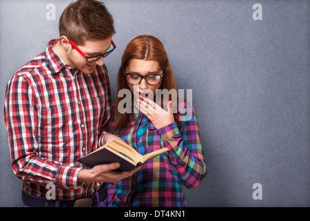 Coppia giovane in abiti eleganti e hipster gli occhiali per leggere un libro. studio shot