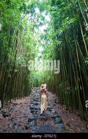 Giovane donna passeggiate nel boschetto di bambù, Maui, Hawaii Foto Stock