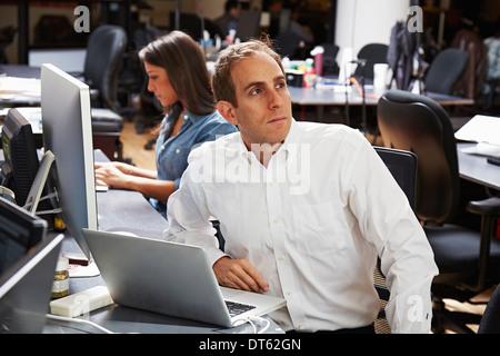 Metà uomo adulto utilizzando computer portatile in ufficio Foto Stock