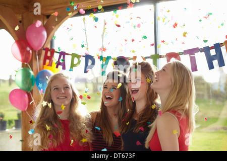 Quattro ragazze adolescenti godendo di coriandoli a festa di compleanno Foto Stock