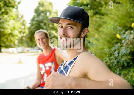 Ritratto di giovani giocatori di basket seduto su una panchina nel parco Foto Stock